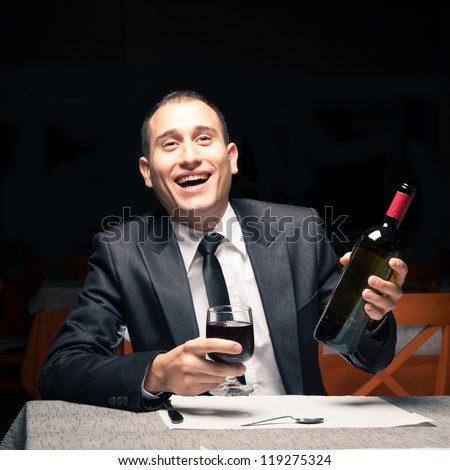 Happy young business man drunk with red wine. - stock photo