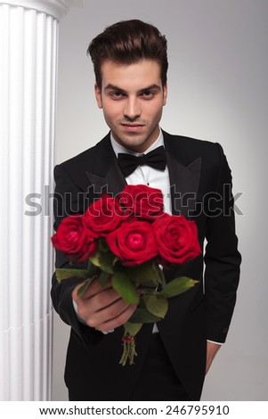 Happy young business man giving you a bouquet of red roses while looking at the camera. - stock photo