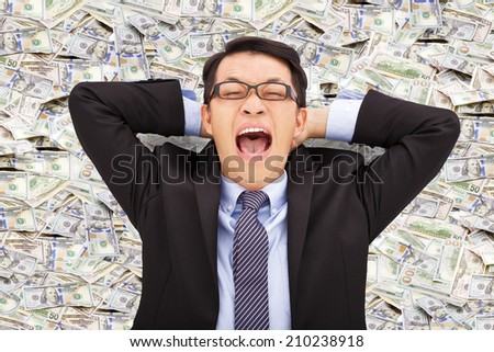 happy young business man lying on the us dollar - stock photo