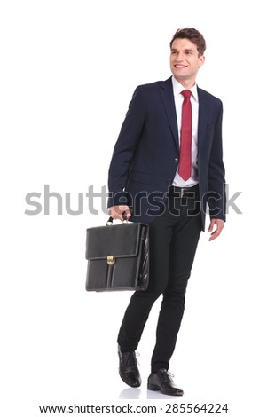Happy young business man walking with a briefcase in his hand while looking away from the camera. - stock photo