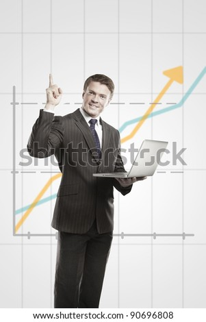 Happy young business man with laptop showing thumbs up. On a gray background with rising arrow, representing business growth - stock photo