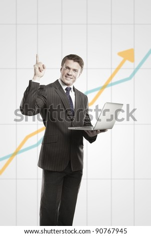 Happy young business man with laptop showing thumbs up. On a gray background with rising arrow, representing business growth