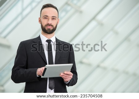 Happy young business man with tablet at work in modern office. - stock photo