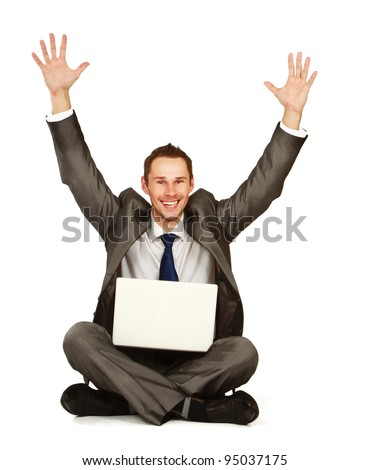 Happy young business man working on a laptop, isolated against white background