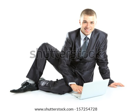 Happy young business man working on a laptop, isolated on white background