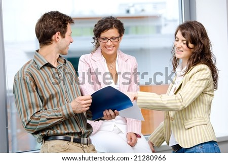 Happy young business people having team meeting at office and reading documents, smiling. - stock photo