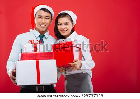Happy young business people holding Christmas gifts and looking at the camera - stock photo