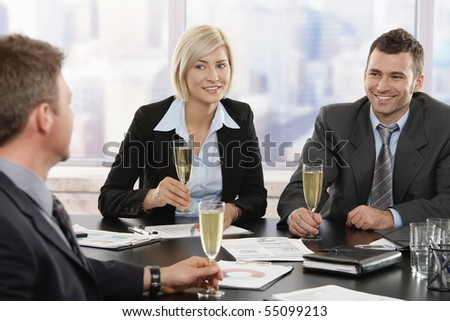 Happy young business people sitting around meeting table at office celebrating success with champagne, smiling.