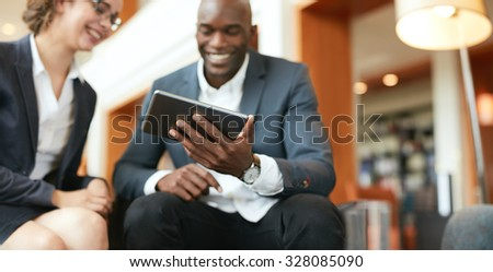 Happy young business people sitting together using digital tablet while at hotel lobby, blurred. - stock photo