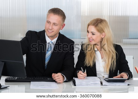 Happy young business people with paperwork discussing over computer at desk in office - stock photo