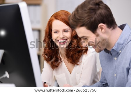 Happy young business team consisting of an attractive redhead woman and man sitting working together in the office - stock photo