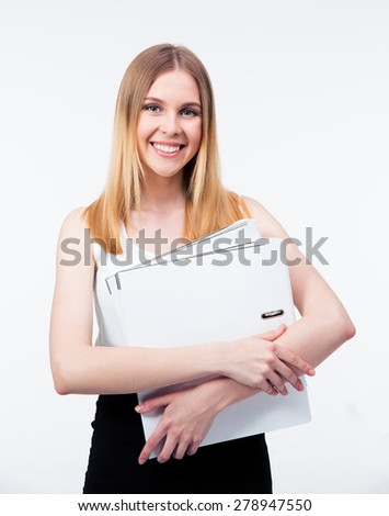 Happy young business woman holding folders over gray background and looking at camera - stock photo