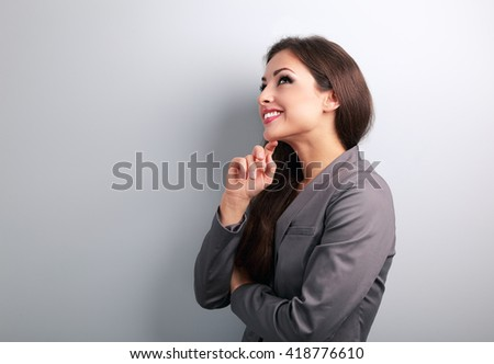 Happy young business woman in suit thinking and looking on empty copy space - stock photo