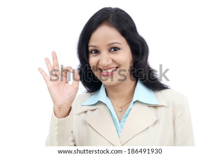 Happy young business woman making Ok gesture against white - stock photo