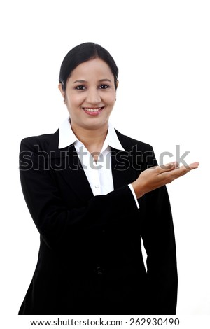 Happy young business woman pointing at copy space - stock photo