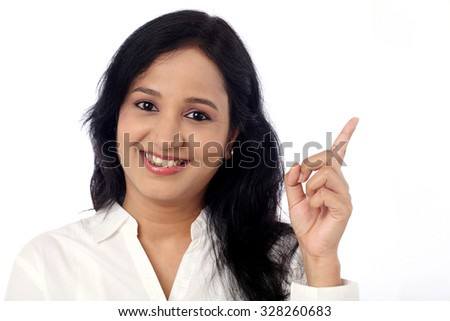 Happy young business woman pointing at copy space