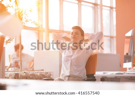 Happy young business woman relaxing and geting insiration while working on desktop computer at modern bright  starup office interior. Morning sunrise or sunset with sun flare in background. - stock photo