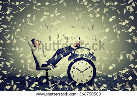 Happy young business woman relaxing sitting in her office under money rain making money dollar bills cash falling down. Stress free time management good earnings profit concept  - stock photo