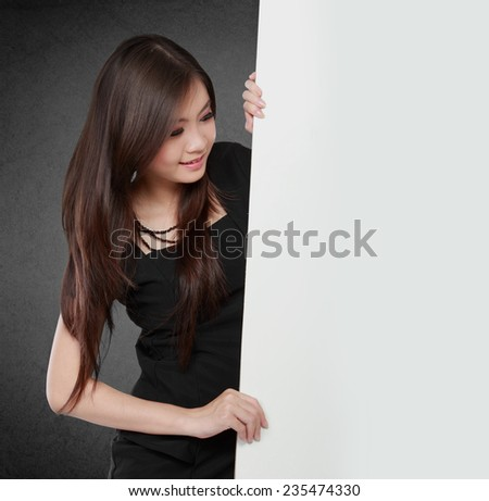 Happy young business woman showing blank signboard, isolated on black background - stock photo