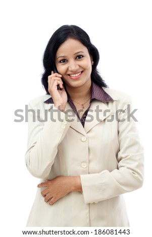 Happy young business woman talking on cell phone against white background