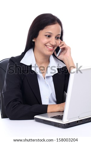 Happy young business woman talking on mobile phone against white