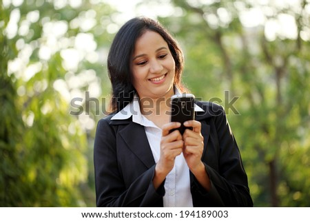 Happy young business woman text messaging at outdoors