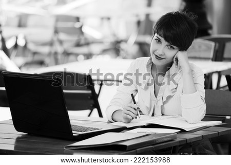 Happy young business woman using laptop in a city cafe  - stock photo