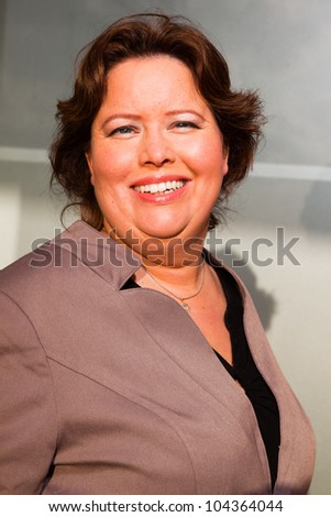 Happy young business woman wearing brown suit. On location. Outdoors. Short brown hair.