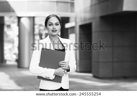 Happy young business woman with a folder at the office building - stock photo