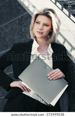 Happy young business woman with a folder standing at office building - stock photo