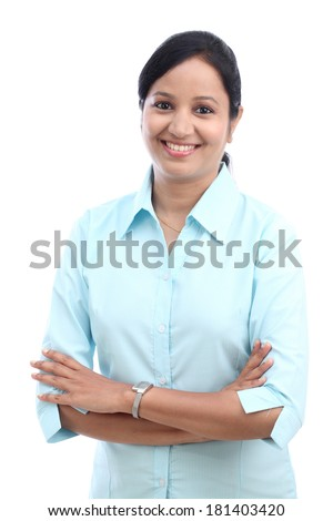 Happy young business woman with arms crossed against white