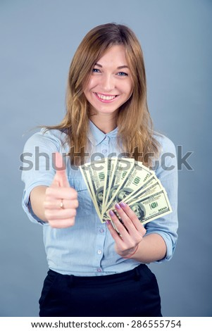 Happy young business woman with gesture thumbs up. Beautiful smiling business woman standing against blue background. Thumb up concept. Woman holding a hundred dollar bills USA. Victory, success. - stock photo