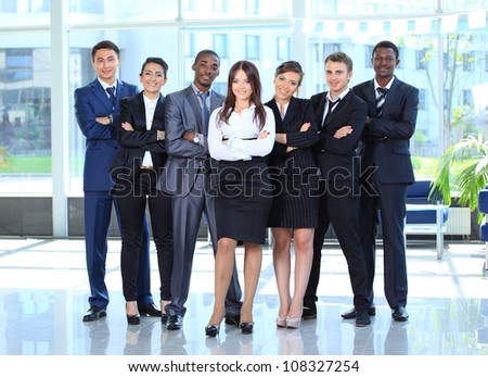 Happy young business woman with her team in background - stock photo