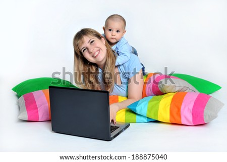 happy young business woman working on a laptop with her baby - stock photo