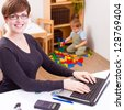 happy young business woman working on a laptop with her child playing at the back - stock photo
