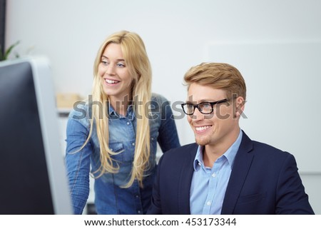 Happy young businessman and woman reading information online on a desktop monitor smiling in satisfaction and pleasure - stock photo