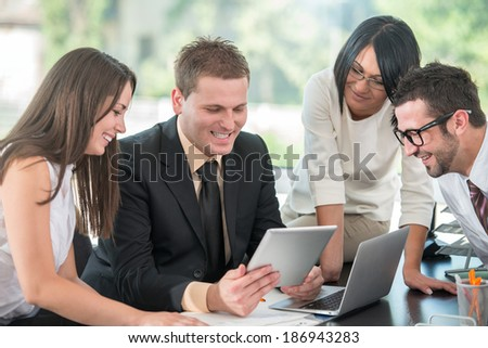 Happy young businessman at work with colleagues