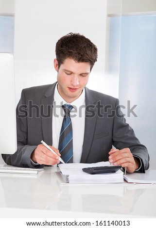 Happy Young Businessman Calculating Bills At Desk
