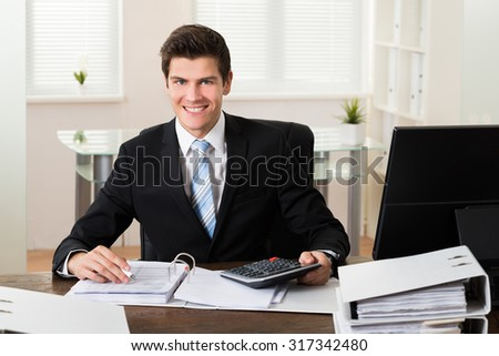 Happy Young Businessman Calculating Financial Data At Desk - stock photo