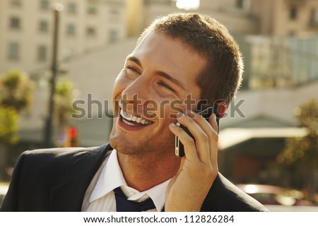 happy young businessman calling with mobile phone . he is calling somebody by mobile telephone on the street - stock photo