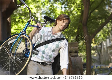 Happy young businessman carrying bicycle outdoors - stock photo
