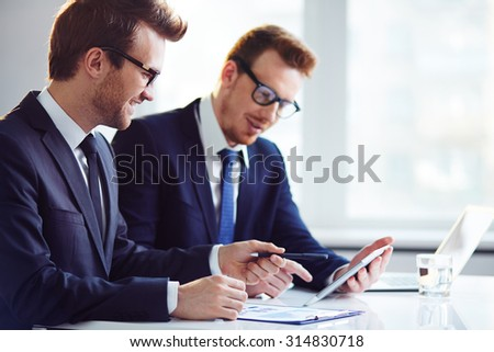Happy young businessman explaining data to his colleague at meeting - stock photo