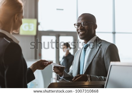 happy young businessman giving passport and ticket to staff at airport check in counter