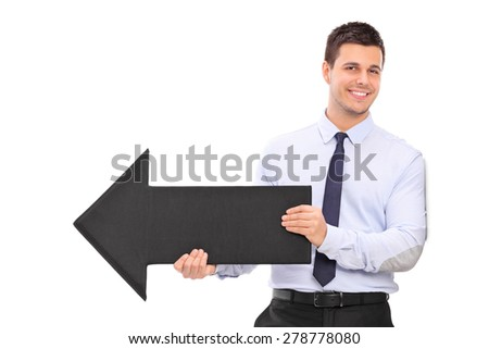 Happy young businessman holding a big black arrow pointing right and leaning against a wall isolated on white background