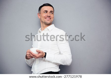 Happy young businessman holding cup of coffee and looking way at copyspace. Standing over gray background