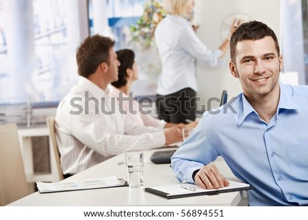 Happy young businessman in business meeting at office, looking at camera smiling.?