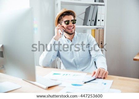 Happy young businessman in sunglases and hat talking on mobile phone and laughing in office - stock photo