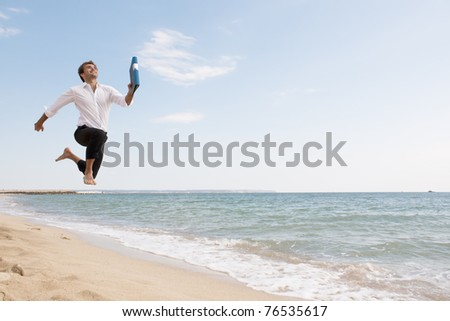 happy young businessman is running on the beach - stock photo
