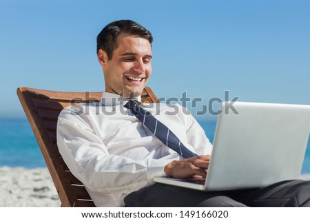 Happy young businessman on a deck chair using his computer on the beach - stock photo