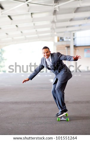 happy young businessman on skateboard - stock photo
